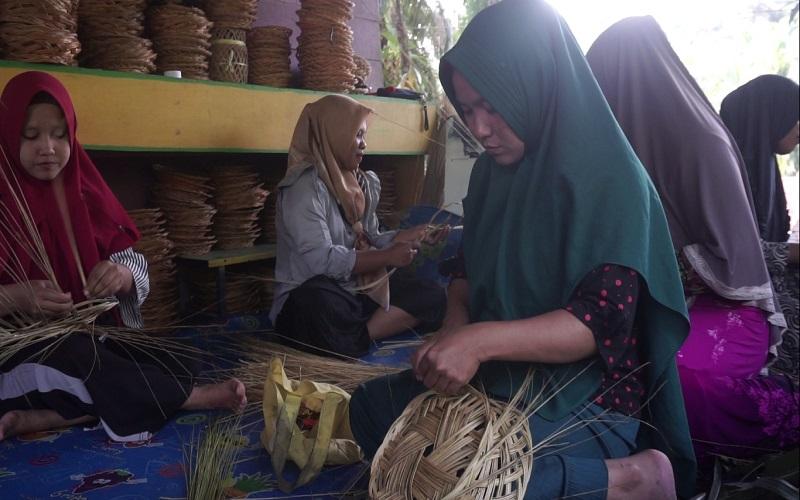 Kegiatan Rini dan Ibu/ibu sedang melakukan proses pembuatan piring anyaman lidi dari pelepah kelapa sawit.