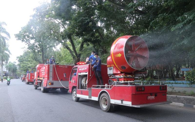 Petugas menyemprot cairan disinfektan di sepanjang jalan protokol Kota Palembang. istimewa