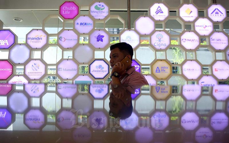Karyawan berkomunikasi didekat logo beberapa perusahaan asuransi di kantor Asosiasi Asuransi Jiwa Indonesia (AAJI) di Jakarta, Selasa (15/1/2019). Bisnis - Nurul Hidayat