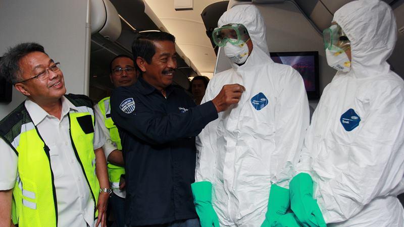 Presiden Direktur Lion Air Edward Sirait (kedua kiri) disaksikan Dirjen Perhubungan Udara Novie Riyanto (kiri) merapikan pakian kabin krew mengenakan baju steril saat melakukan persiapan akhir didalam pesawat tipe A-330 milik Batik Air ID 8618 yang akan digunakan untuk menjemput Warga Negara Indonesia (WNI) di Wuhan, China, di Bandara Soekarno-Hatta, Tanggerang, Sabtu (1/2/2020). -  ANTARA / Muhammad Iqbal