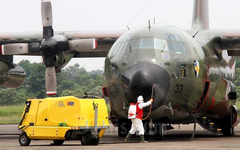 Petugas menyemprotkan cairan disinfektan ke Pesawat Hercules C-130 milik TNI-AU yang baru mendarat di Landasan Udara (Lanud) Halim Perdanakusuma, Jakarta, Senin (23/3/2020). Pemerintah mendatangkan 9 ton peralatan medis dari Shanghai, China untuk mengatasi penyebaran virus corona (covid-19) di Indonesia, yang dibawa menggunakan pesawat Hercules C-310. Bisnis - Arief Hermawan P