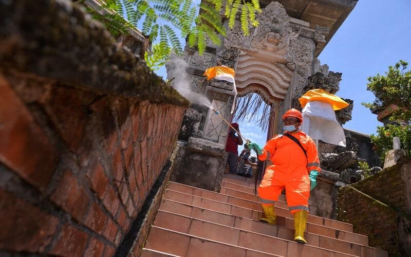 Petugas menyemprotkan cairan disinfektan di Pura Jagadhita, Manado, Sulawesi Utara, Rabu (18/3/2020). Polda Sulut bekerjasama dengan Kodam XIII/Merdeka, Lantamal VII dan Lanud Sam Ratulangi melaksanakan penyemprotan cairan disinfektan di tempat peribadahan untuk mencegah penularan virus Corona 2019 (COVID-19). - Antara/Adwit B Pramono