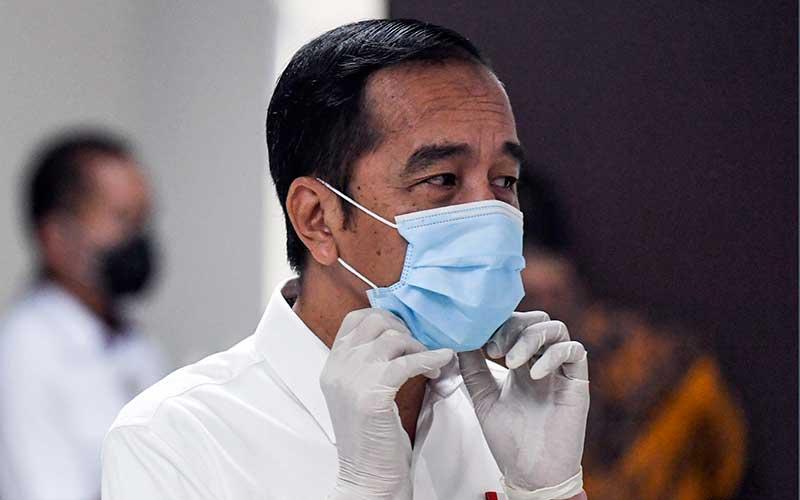 Presiden Joko Widodo merapikan masker yang digunakannya saat meninjau Rumah Sakit Darurat Penanganan COVID-19 Wisma Atlet Kemayoran, Jakarta, Senin (23/3/2020). - Antara/Hafidz Mubarak