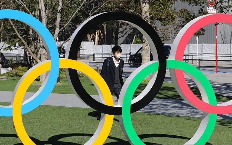Seorang pejalan kaki sambil mengenakan masker melintas di dekat logo olimpiade di kota Tokyo, Jepang (12/3/2020) - Antara.