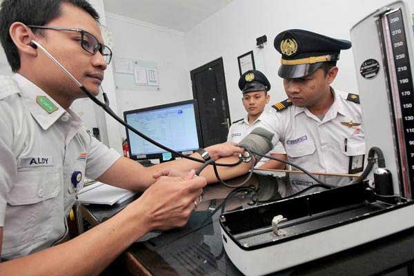 Paramedis mengukur tekanan darah masinis kereta api di Stasiun Pasar Turi, Surabaya, Jawa Timur, Rabu (14/6). - Antara/Didik Suhartono