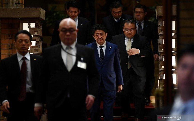 Perdana Menteri Jepang Shinzo Abe (tengah) bersiap memberi keterangan pers di Tokyo, Jepang, Selasa (24/3/2020). Perdana Menteri Jepang Shinzo Abe dan Presiden IOC Thomas Bach sepakat bahwa penyelenggaraan Olimpiade 2020 Tokyo ditunda setahun terkait pandemi COVID-19. - Antara/Charly Triballeau via Reuters