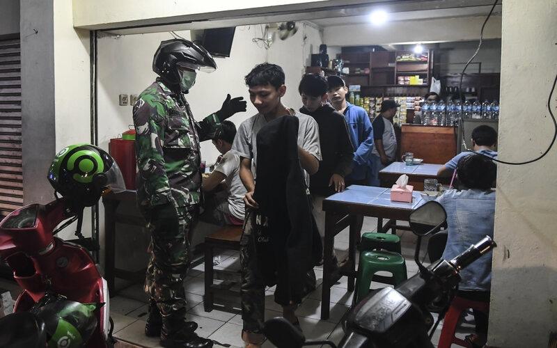 Petugas TNI membubarkan warga yang masih berkumpul saat melakukan razia cegah penyebaran Covid-19 di kawasan Kemang, Jakarta, Selasa (24/3/2020). Dalam razia tersebut petugas meminta warga untuk tidak berkumpul dalam keramaian dan dihimbau untuk pulang ke rumah masing-masing sesuai instruksi pemerintah agar melakukan