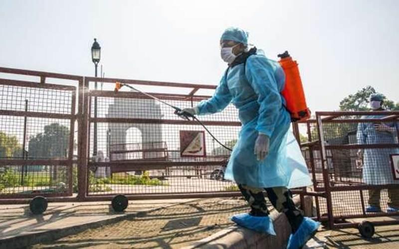 Petugas menyemprotkan disinfektan di dekat monumen India Gate di New Delhi, 22 Maret 2020./Prashanth Vishwanathan - Bloomberg
