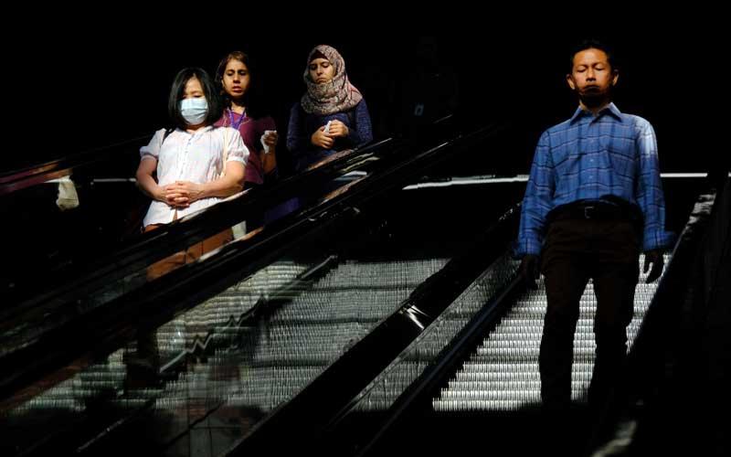 Ilustrasi-Warga menggunakan masker saat menggunakan eskalator di Stasiun Ampang Park, Kuala Lumpur, Malaysia, Selasa (17/3/2020). - Bloomberg/Samsul Said