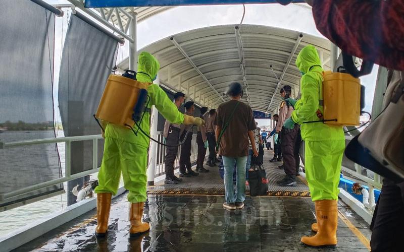 Sebanyak 81 TKI Malaysia bermasalah tiba di Pelabuhan Internasional Batam Centre, Selasa (24/3/2020). Mereka disemprot desinfektan saat keluar dari kapal. - Bisnis/Bobi Bani.