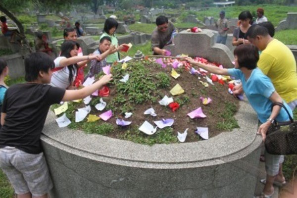 Sejumlah warga Tionghoa meletakkan kertas di makam leluhurnya sebagai ritual Hari Raya Ceng Beng, di Sentong, Batu, Jawa Timur, Sabtu (30/3/2013). - Antara/Ari Bowo Sucipto