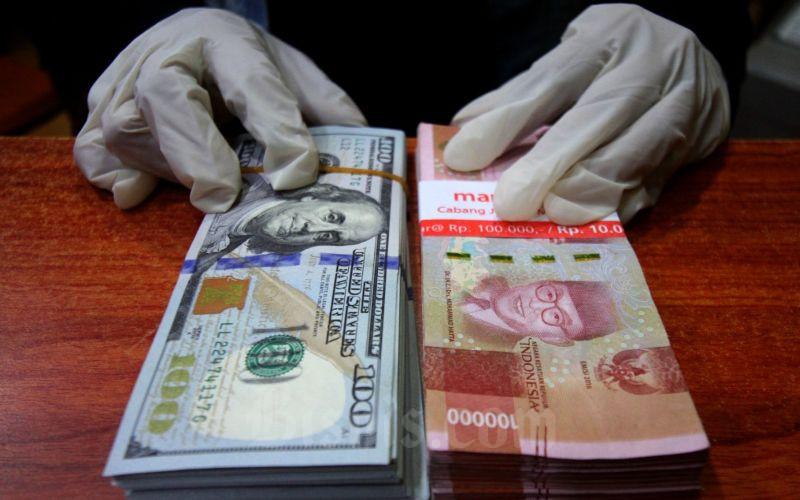 Petugas menunjukkan uang rupiah dan dolar AS di salah satu gerai penukaran mata uang asing di Jakarta, Kamis (19/3/2020). - Bisnis/Arief Hermawan P