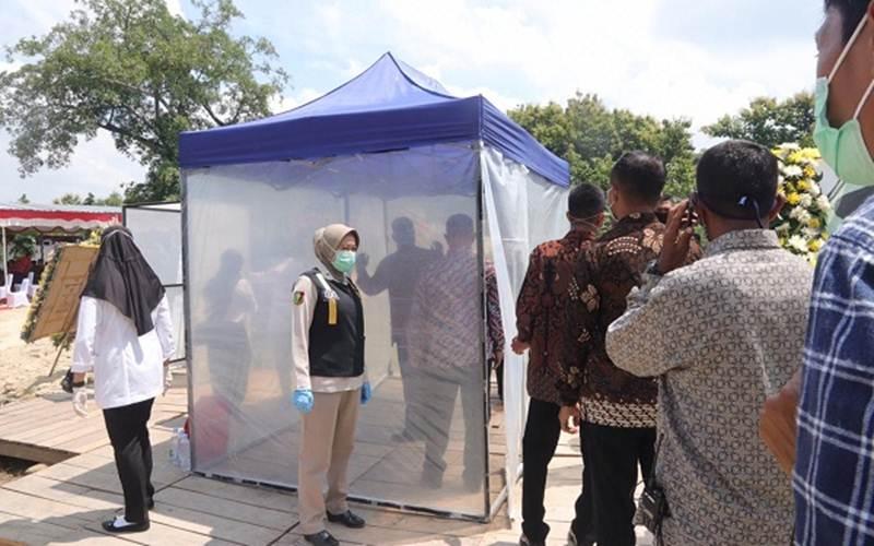 Pelayat Ibunda Presiden Jokowi melakukan cek kesehatan di Pemakaman Keluarga Mundu, Selokaton, Gondangrejo, Kabupaten Karanganyar, Kamis (26/3/2020). - Solopos/Sunaryo Haryo Bayu