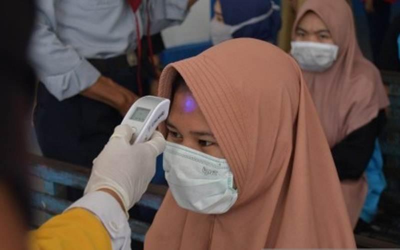 Petugas Kesehatan memeriksa suhu tubuh rombongan siswa penumpang angkutan darat saat transit di Terminal Mamboro, Palu, Sulawesi Tengah, Selasa (24/3/2020). Pemerintah Sulawesi Tengah memperketat pintu keluar dan masuk daerah tersebut dengan memeriksa kesehatan setiap warga yang melintas guna mengantisipasi penyebaran virus Corona (COVID-19). - ANTARA/Mohamad Hamzah