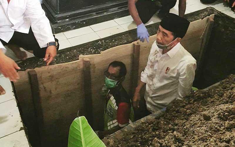 Presiden Joko Widodo berada di dalam liang lahat saat prosesi pemakaman ibu nya di Karanganayar, Jawa Tengah, Kamis (26/3 - 2020). Istimewa