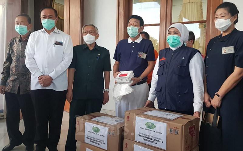 Gubernur Jatim Khofifah Indar Parawansa menerima bantuan APD dan masker dari Yayasan Buddha Tzu Chi Indonesia di Gedung Grahadi Surabaya, Kamis (26/3/2020). - Bisnis/Peni Widarti
