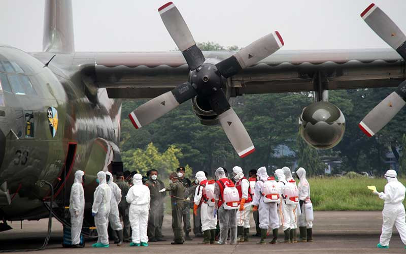 Sejumlah petugas disemprot cairan disinfektan sebelum memindahkan muatan dari Pesawat Hercules C-130 yang baru mendarat di Landasan Udara (Lanud) Halim Perdanakusuma, Jakarta, Senin (23/3/2020). Pemerintah mendatangkan 9 ton peralatan medis dari Shanghai, China untuk mengatasi penyebaran virus corona (covid-19) di Indonesia, yang dibawa menggunakan pesawat Hercules C-310. Bisnis - Arief Hermawan P