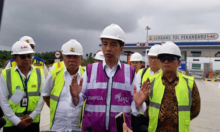 Presiden Joko Widodo (ketiga kiri) didampingi Menteri PUPR Basuki Hadimuljono (kedua kiri) menjawab pertanyaan wartawan sesuai meninjau progres pembangunan ruas Tol Pekanbaru-Dumai di Provinsi Riau, Jumat (21/2 - 2020). Ruas tol Pekanbaru/Dumai ditargetkan rampung pada April 2020. Peningkatan infrastruktur termasuk lewat Trans Sumatra diharapkan bisa meningkatkan perekonomian dan dongkrak daya saing Indonesia. Bisnis/Agne Yasa.