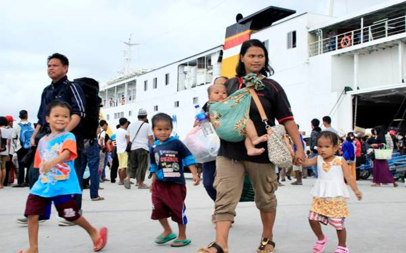 Seorang ibu dengan anak-anaknya yang bekerja di Negeri Sabah, Malaysia turun dari kapal saat tiba di Pelabuhan Tunon Taka Kabupaten Nunukan, Kaltara, Senin (30/1). - Antara/M Rusman
