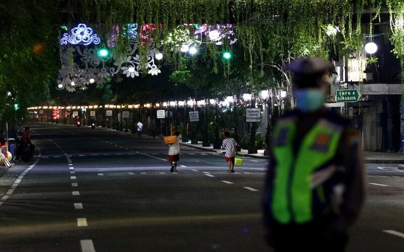 Polisi berjaga di Jalan Tunjungan, Surabaya, Jawa Timur, Jumat (27/3/2020) malam. Polrestabes Surabaya memberlakukan kawasan tertib 'physical distancing' atau jaga jarak secara fisik di Jalan Tunjungan dan Jalan Raya Darmo pada hari Jumat, Sabtu dan Minggu pada jam tertentu dengan tidak memperbolehkan kendaraan melintas atau orang berkumpul guna mencegah penyebaran virus Corona atau COVID-19. - Antara/Didik Suhartono