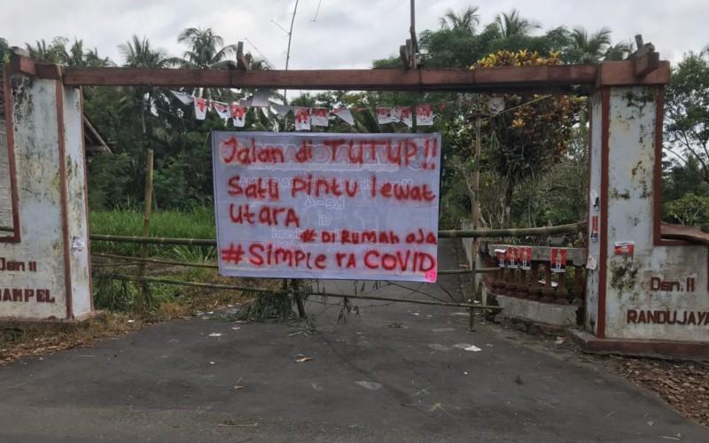 Spanduk warga di Desa Ngampel, Harjobinangun, Sleman Yogyakarta. Warga melakukan inisiatif untuk menutup akses jalan, dan memusatkan lalu lintas warga melalui satu pintu. - Bisnis/Istimewa