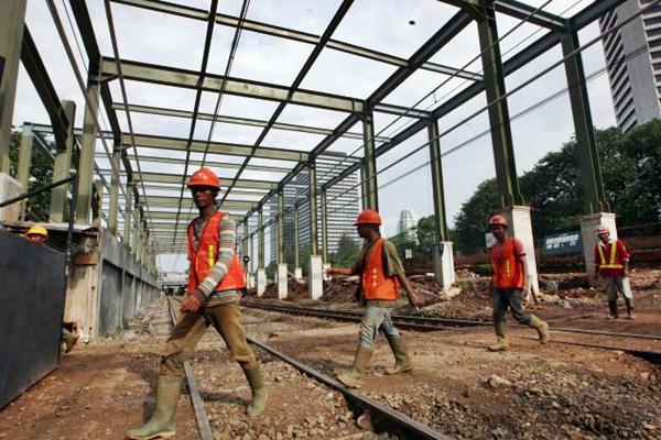 Pekerja berjalan melewati rel kereta api di Jakarta, Selasa (14/3). - JIBI/Dedi Gunawan