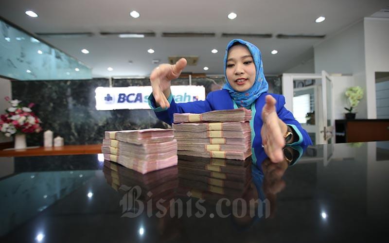 Ilustrasi - Karyawan menghitung uang rupiah di kantor cabang Bank BCA Syariah di Jakarta, Selasa (7/1/2020) -  Bisnis/Abdullah Azzam