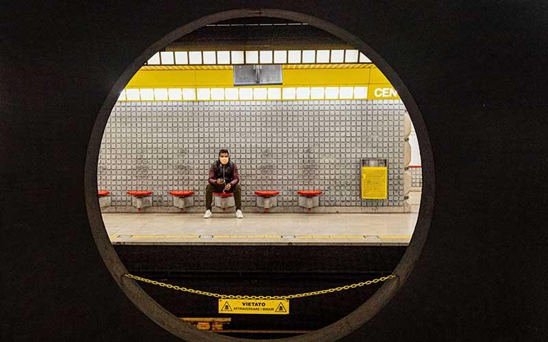 Penumpang kereta menggunakan masker saat menunggu kereta di peron kereta bawah tanah Metro Milan di Milan, Italia, Kamis (12/3/2020). Italia menghentikan kehidupan normal dan hanya memberikan akses terhadap layanan-layanan penting untuk membendung penyebaran virus corona yang mematikan. - Bloomberg/Alberto Bernasconi