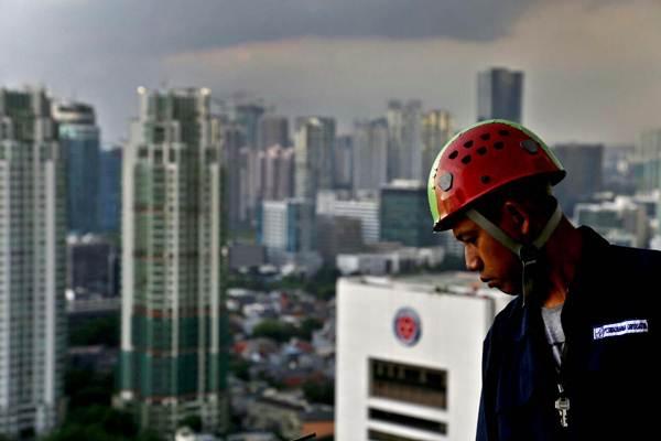 Pekerja melakukan perawatan rutin pada salah satu gedung bertingkat di Jakarta, Rabu (22/11). - JIBI/Nurul Hidayat
