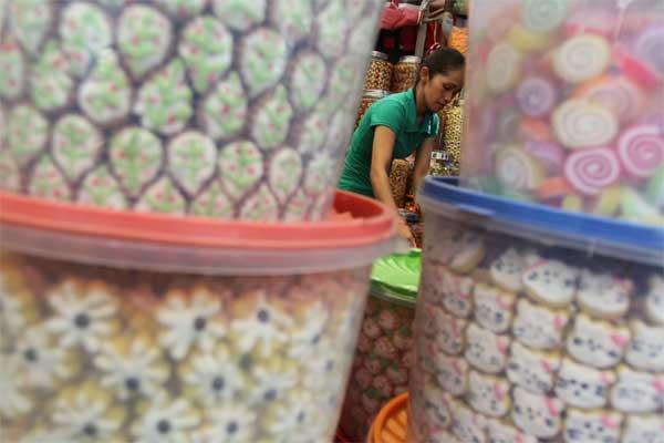 Pedagang menata aneka ragam kue kering yang dijual di pasar Sukaramai Pekanbaru, Riau, Minggu (11/6). - Antara/Rony Muharrman