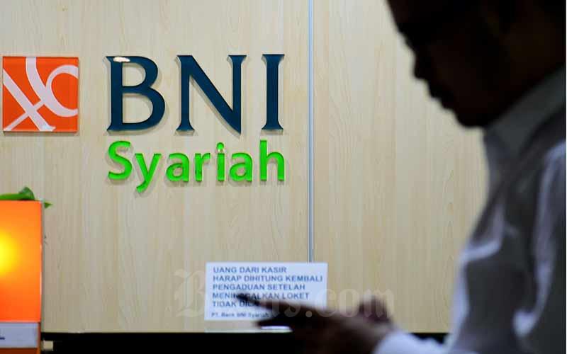 Nasabah berkomunikasi di dekat logo BNI Syariah di Jakarta, Senin (2/3/2020). Bisnis - Abdurachman