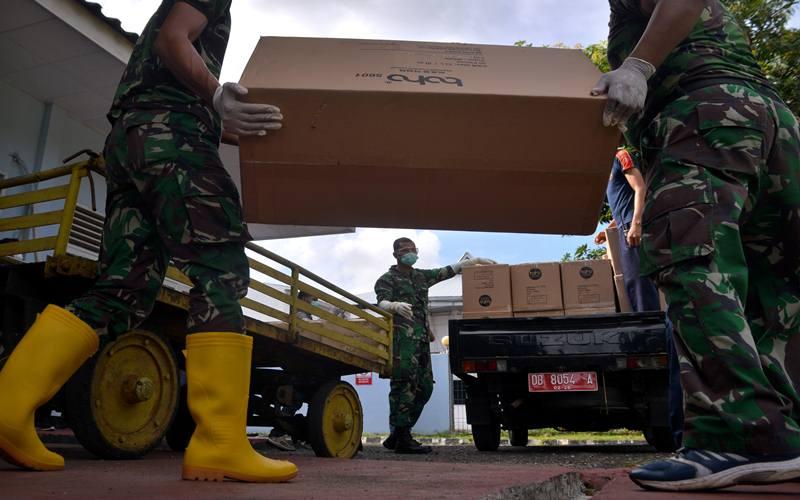 Prajurit TNI mengangkat kardus berisi Alat Perlindungan Diri (APD) untuk penanganan COVID-19 di Bandara Sam Ratulangi, Manado, Kamis (26/3/2020). Pemerintah Provinsi Sulawesi Utara menerima sekitar 3.000 APD yang akan didistribusikan ke rumah sakit rujukan penanganan COVID-19 di Sulut. ANTARA FOTO - Adwit B Pramono