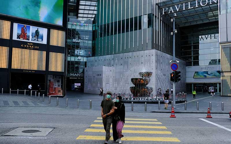 Warga menggunakan masker menyeberang jalan yang kosong di Bukit Bintang di Kuala Lumpur, Malaysia, Rabu (18/3/2020). Sejumlah jalan raya di Malaysia menjadi sepi setelah pemerintah mengumumkan lockdown nasional selama dua minggu. Bloomberg - Samsul Said