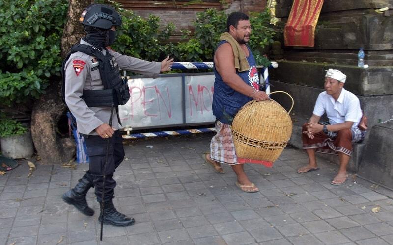 Anggota Brimob Polda Bali membubarkan warga yang menggelar sabung ayam di Denpasar, Bali, Selasa (24/3/2020). Polisi menertibkan warga yang berkerumun tersebut untuk pencegahan penyebaran Covid-19. - Antara/Nyoman Hendra Wibowo