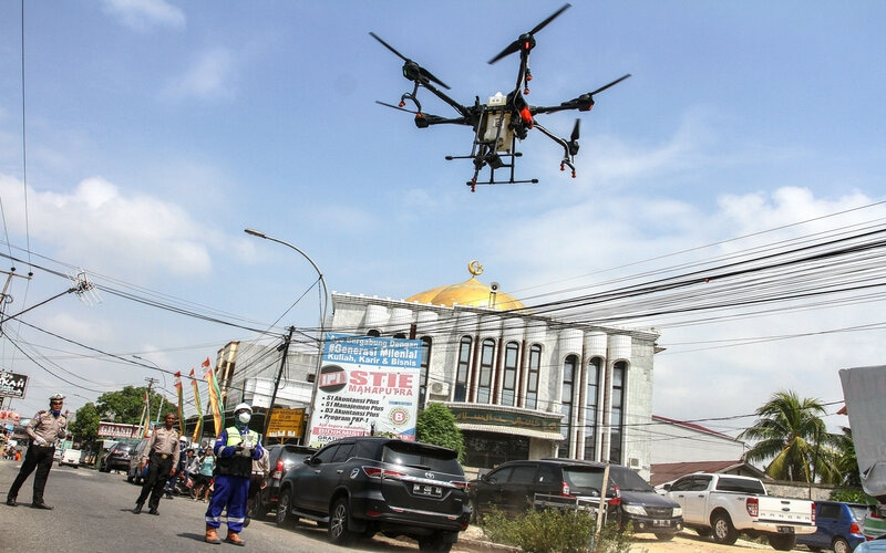 Tim gabungan Polda Riau beserta Polresta Pekanbaru mengoperasikan drone (pesawat tanpa awak) untuk menyemprotkan cairan disinfektan di kawasan pemukiman penduduk di Pekanbaru, Riau, Rabu (25/3/2020). Penyemprotan disinfektan tersebut dilakukan guna menekan penyebaran virus Corona (Covid-19). - Antara/Rony Muharrman
