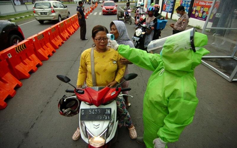 Petugas dinas kesehatan memeriksa suhu tubuh warga yang akan masuk ke Kota Tegal di Jawa Tengah, Selasa (31/3/2020). Pemeriksaan kesehatan warga yang akan masuk ke Kota Tegal pascakarantina wilayah tersebut untuk antisipasi penyebaran Covid-19. - Antara/Oky Lukmansyah