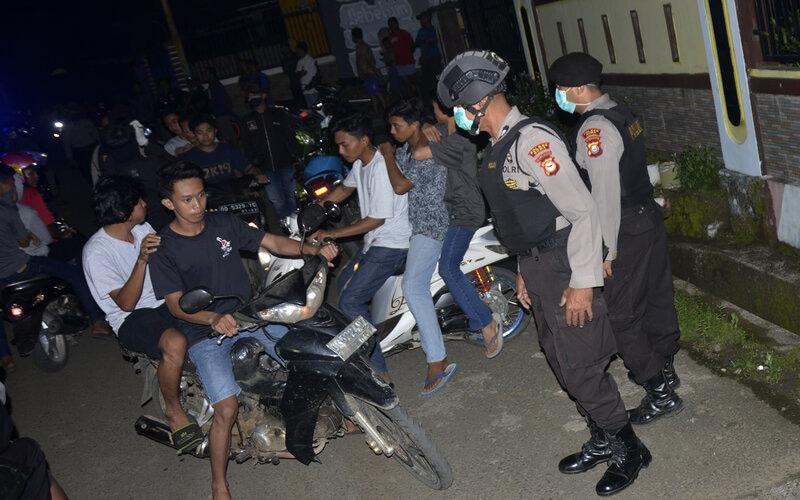 Petugas kepolisian membubarkan warga yang berkumpul di pinggir jalan di Kabupaten Gowa, Sulawesi Selatan, Minggu (29/3/2020) malam. Patroli malam yang dilakukan Polres Gowa tersebut terkait imbauan pemerintah agar warga mengurangi interaksi di luar rumah sebagai upaya mencegah penyebaran Covid-19. - Antara/Abriawan Abhe