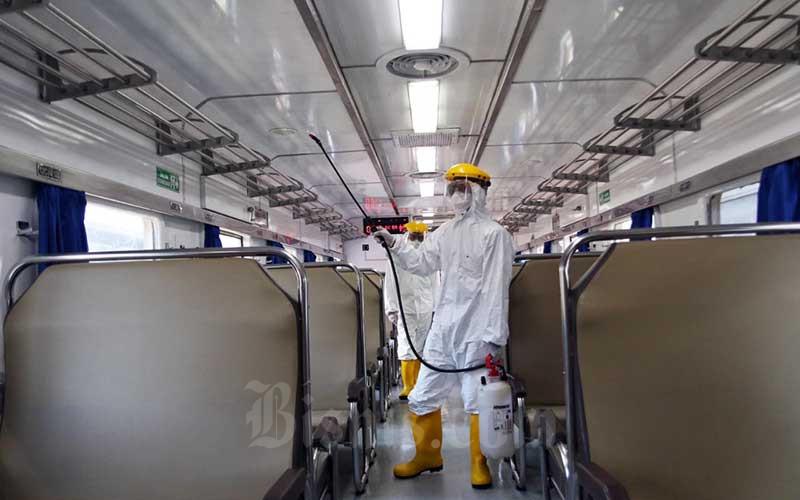 Petugas saat melakukan penyemprotan disinfektan pada gerbong kereta api  - Bisnis/Eusebio Chrysnamurti