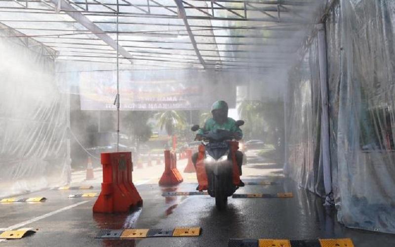 Pengendara sepeda motor melintasi gerbang sterilisasi di Kawasan Pondok Indah, Jakarta, Selasa (31/3/2020). Setiap warga yang memasuki kawasan perumahaan itu diwajibkan untuk masuk ke dalam gerbang sterilisasi untuk disemprotkan cairan disinfektan guna mencegah penyebaran virus corona (COVID-19). - Bisnis