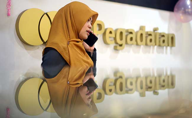 Karyawan melintas didekat logo  PT Pengadaian (Persero) di Jakarta, Senin (17/2/2020). Bisnis - Abdullah Azzam