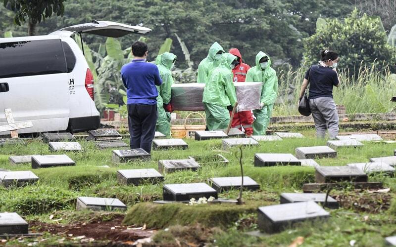 Petugas pemakaman membawa peti jenazah pasien COVID-19 di TPU Pondok Ranggon, Jakarta, Senin (30/3/2020). - Antara/Muhammad Adimaja