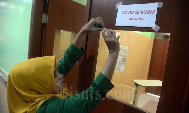 Petugas medis menempelkan stiker di salah satu ruangan isolasi penanganan pasien terinfeksi virus corona. - Antara/Ampelsa