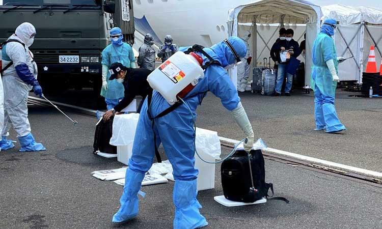 Petugas kesehatan menyemprotkan cairan disinfektan kepada WNI ABK Diamond Princess dan barang bawaan saat turun dari kapal di Yokohama, Jepang, Minggu (2/3/3030). Pemerintah mengevakuasi 69 WNI ABK Diamond Princess yang dinyatakan negatif COVID-19 untuk dipulangkan ke tanah air dan diosevasi di pulau Sebaru Kecil, Kepulauan Seribu. ANTARA FOTO/HO - KBRI Tokyo