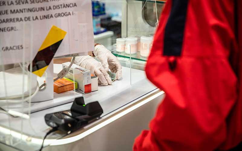 Pekerja farmasi mengenakan sarung tangan bedah untuk melayani pelanggan yang membayar dengan uang tunai di apotek di Barcelona, Spanyol, Minggu (15/3/2020). Spanyol mengumumkan keadaan darurat segera selama 15 hari, yang secara signifikan membatasi mobilitas warga di negara tersebut. Perdana Menteri Pedro Sanchez dalam pidato menyatakan aksi tersebut bertujuan untuk menghentikan penyebaran virus corona. Bloomberg - Angel Garcia