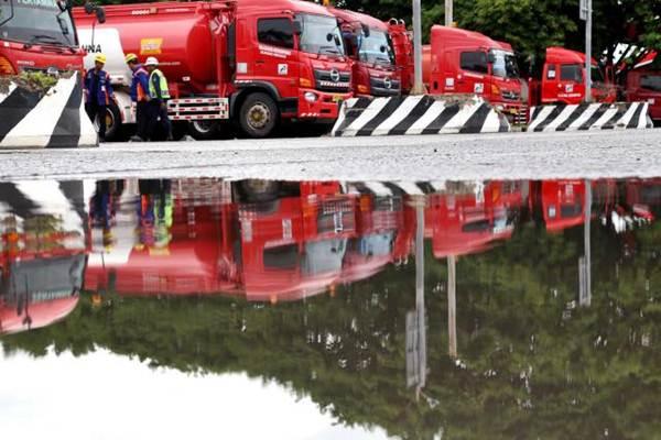 Awak mobil tangki (AMT) bersiap melakukan pengisian bahan bakar minyak ke dalam mobil tangki Pertamina di Terminal BBM Jakarta Group Plumpang, Jakarta Utara, Senin (27/11). - JIBI/Nurul Hidayat