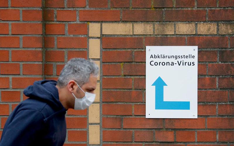 Seorang lelaki mengenakan masker berjalan melewati papan petunjuk yang memandu orang ke pintu masuk stasiun penguji korona di sebuah rumah sakit di Berlin, Jerman. - Bloomberg