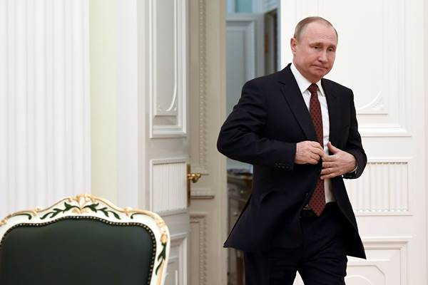 Presiden Rusia Vladimir Putin memasuki aula untuk bertemu dengan kandidat yang berpartisipasi dalam pemilihan presiden sesi terakhir, di Kremlin di Moskow. - Reuters