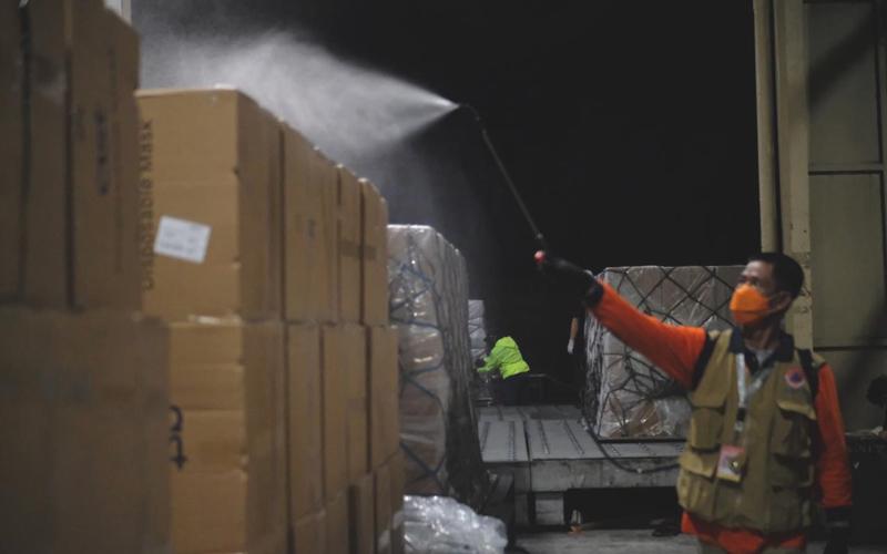 Seorang petugas bandara melakukan penyemprotan disinfektan pada masker-masker yang diimpor oleh Gojek yang baru tiba di Bandara Soekarno Hatta. - Dok. Istimewa/Gojek