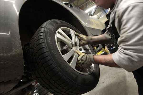 Mengganti ban mobil. - Reuters
