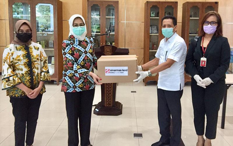Sinar Mas Land diwakili oleh Kepala Divisi Corporate Affairs Dony Martadisata (kanan) menyerahkan bantuan 100 palet alat perlindungan diri (APD) ke Wali Kota Tangerang Selatan Airin Rachmi Diany (kiri). - Istimewa